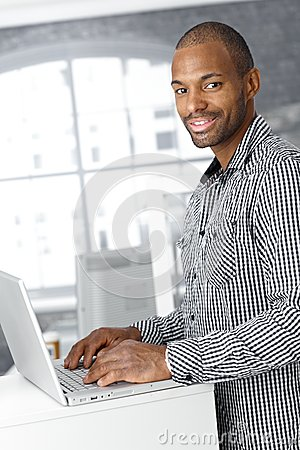 Portrait of ethnic office worker with laptop