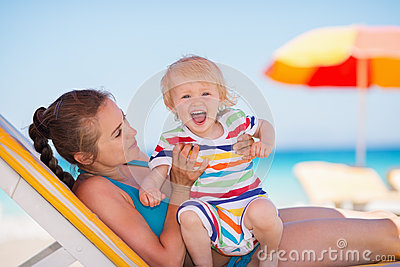 Portrait of excited baby with mother on beach