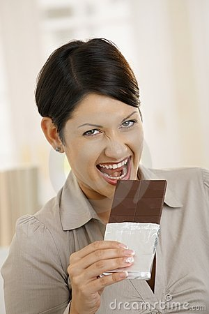 Portrait of excited woman biting chocolate
