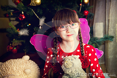 Portrait of fairy girl in front of Christmas tree
