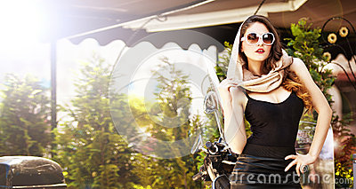 Portrait of fashion attractive girl with headscarf and sunglasses besides an old scooter