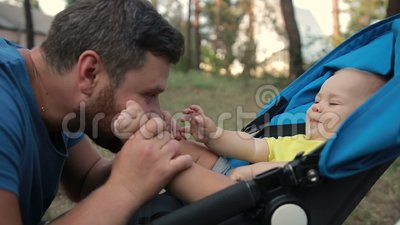 Portrait of father kissing baby son`s feet stock video footage
