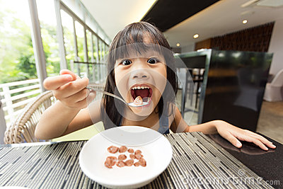 Portrait of feeling happy a young girl having breakfast on table Stock Photo