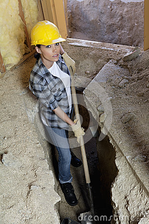 Portrait of female worker digging with shovel at construction site