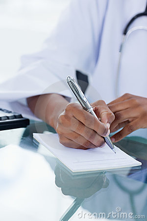 Portrait of a feminine hand writing a prescription