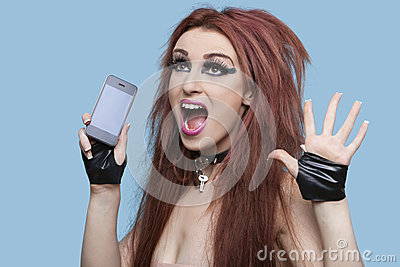 Portrait of funky young woman screaming while using cell phone over blue background