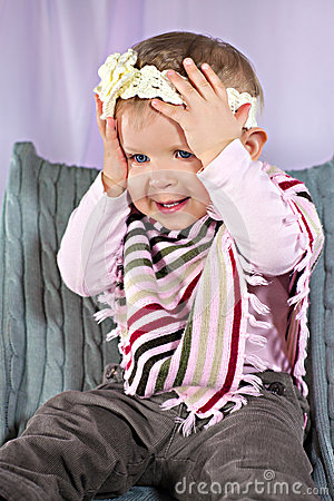 Funny baby girl with hands on her head