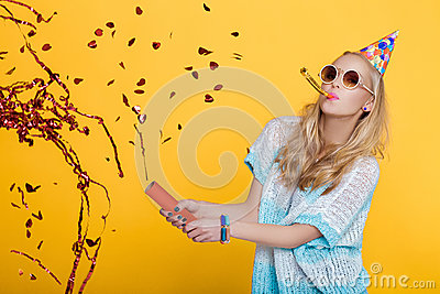 Portrait of funny blond woman in birthday hat and red confetti on yellow background. Celebration and party. Stock Photo