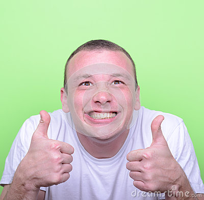 Portrait of with funny expression holding thumbs up against gree
