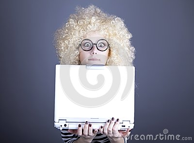 Portrait of funny girl in blonde wig with laptop.