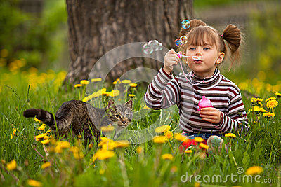Portrait of funny little girl blowing soap bubbles