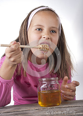 Portrait of funny lovely little girl eat honey