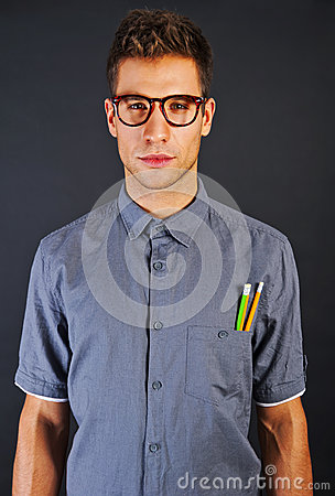 Portrait of funny nerd man with pencyls and glasses over black b