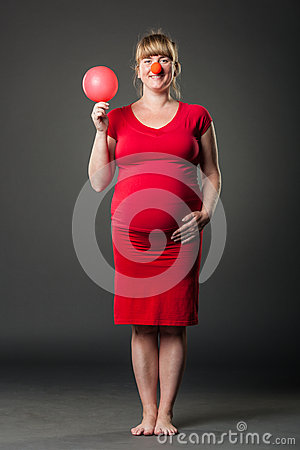 Portrait of funny pregnant woman in red dress
