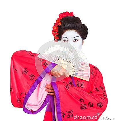 Portrait of geisha hiding behind fan