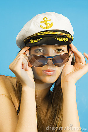 Portrait of the girl in dark glasses and a sea peak-cap