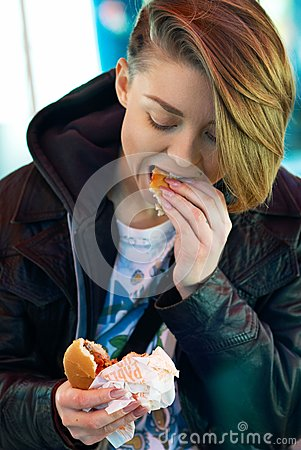 Portrait of girl with eats burger on the terrace