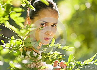 Portrait of girl hiding in foliage