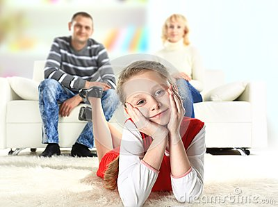 A portrait of a girl lying on the floor and smiling with her parents