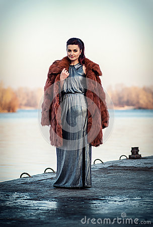 Portrait of the glamorous brunette lady in expensive fur coat watching river. Stock Photo
