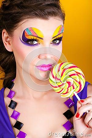 Portrait of a glamourous woman holding lollipop