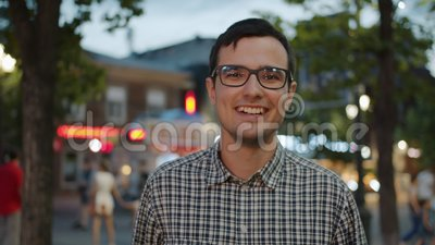 Portrait of good-looking student in glasses laughing in city street in the evening. Portrait of good-looking male student in stylish glasses laughing in city stock video