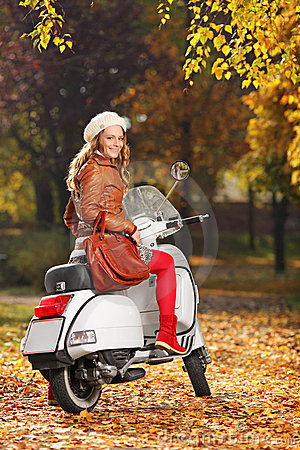 Portrait of gorgeous woman on a scooter