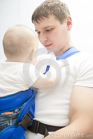 Portrait of handsome father holding son in sling