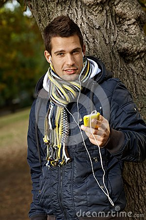 Portrait of handsome guy with mp3 player outdoors