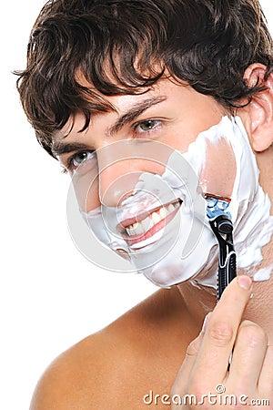 Portrait of handsome man shaving his face