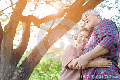 Portrait happiness older couple. Charming grandfather and grandmother is embracing each other with love and smiley faces in a park Stock Photo