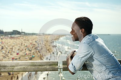 Portrait of a happy african american man smiling at the beach