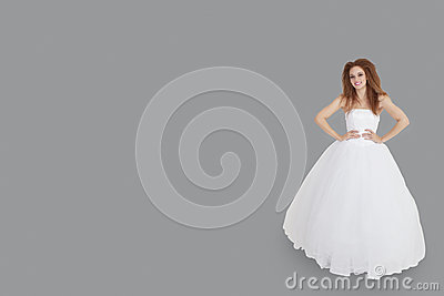 Portrait of happy brunette in wedding dress with hands on hips standing over gray background