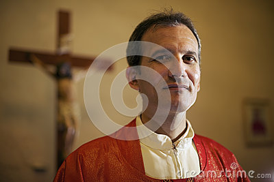 Portrait of happy catholic priest smiling at camera in church