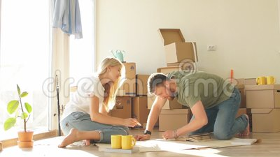 Couple looking blueprints of they new house. Planning interior design. Portrait of happy caucsian couple planning new house design looking at paper stock video footage