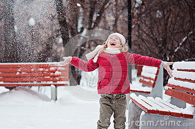 Portrait of happy child girl throwing snow on the walk in winter park