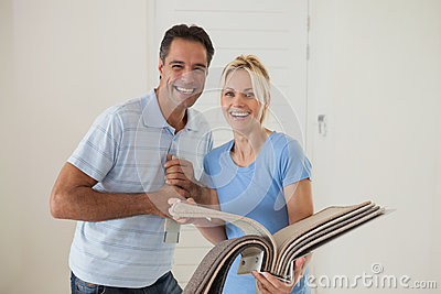 Portrait of a happy couple with color book in new house