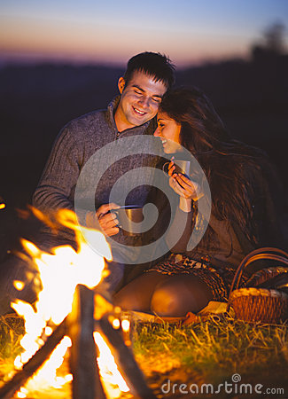 Portrait of the happy couple sitting by fire on autumn beach Stock Photo