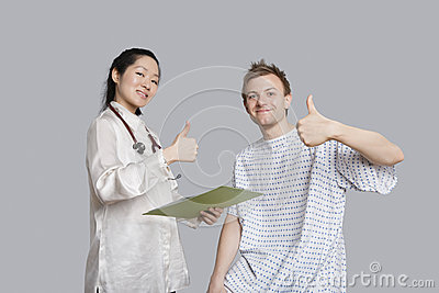 Portrait of happy doctor and patient gesturing thumbs up