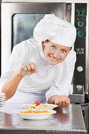 Happy Chef Adding Spices To Dish