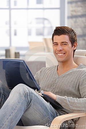 Portrait of happy guy with laptop computer