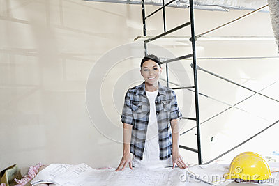 Portrait of a happy mid adult woman with building plans at construction site