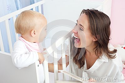 Portrait of a happy mother laughing with cute baby in crib
