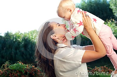 Portrait of a happy mother lifting cute baby