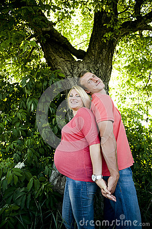 Portrait of a happy pregnant couple back to back