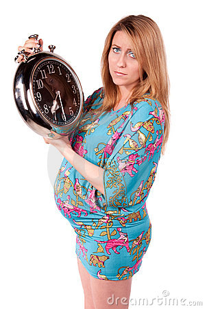 Portrait of happy pregnant woman with clock