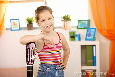 Portrait of happy schoolgirl with guitar