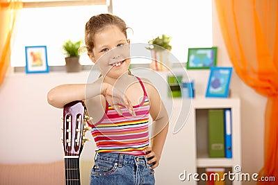 Portrait of happy schoolgirl with guitar