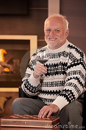 Portrait of happy senior man having wine