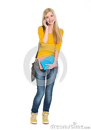 Portrait of happy student girl speaking mobile